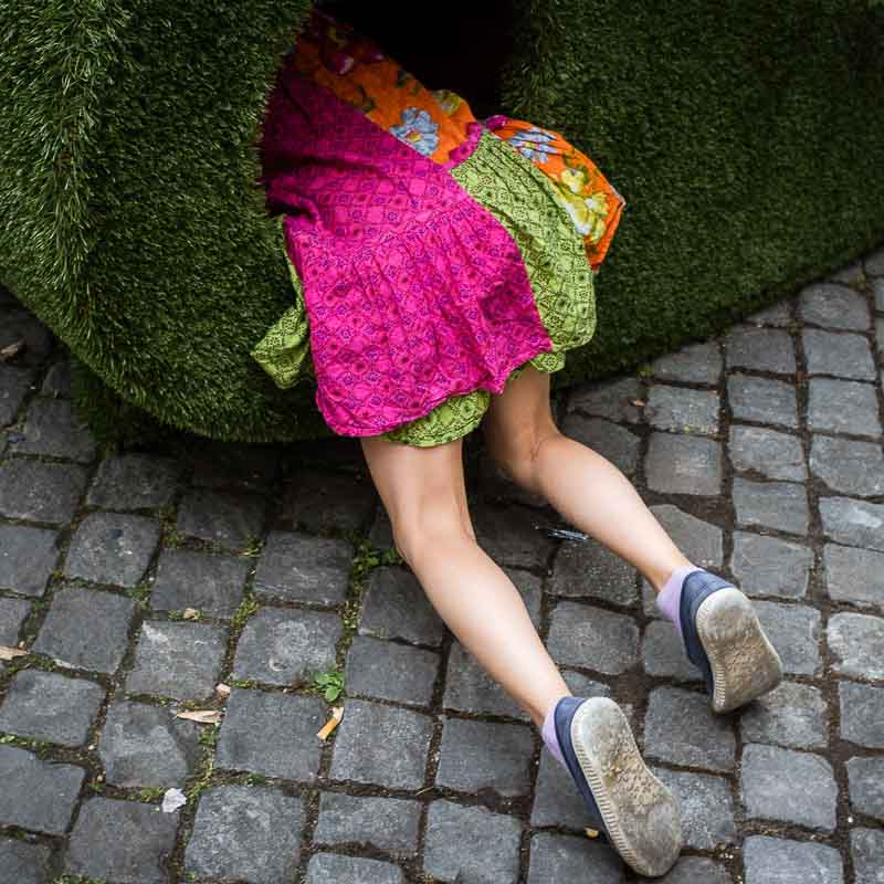 Street Photography - Keep me alive. Image 1 of 24. Taken in Geneva, Switzerland by Dani Oshi. Street Photograph of a girl on a pink dress entering some sort of a hole in a green structure. Reminder of Alice in Wonderland