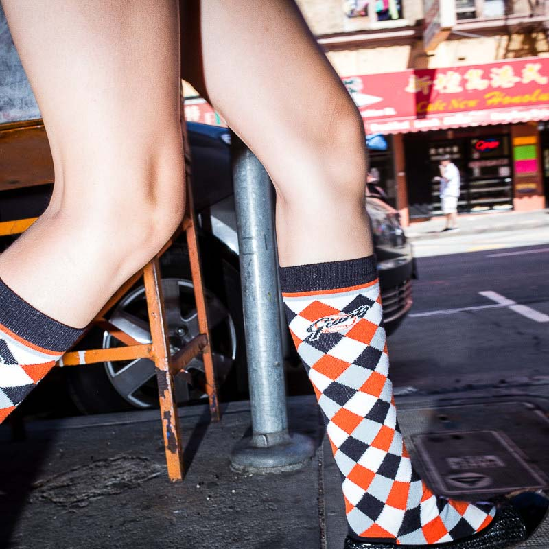 Street Photography - Understatement. Image 1 of 24. Taken in San Francisco, United States by Dani Oshi. Close up flash street photograph of a pair of legs of someone with high colored socks walking on the streets