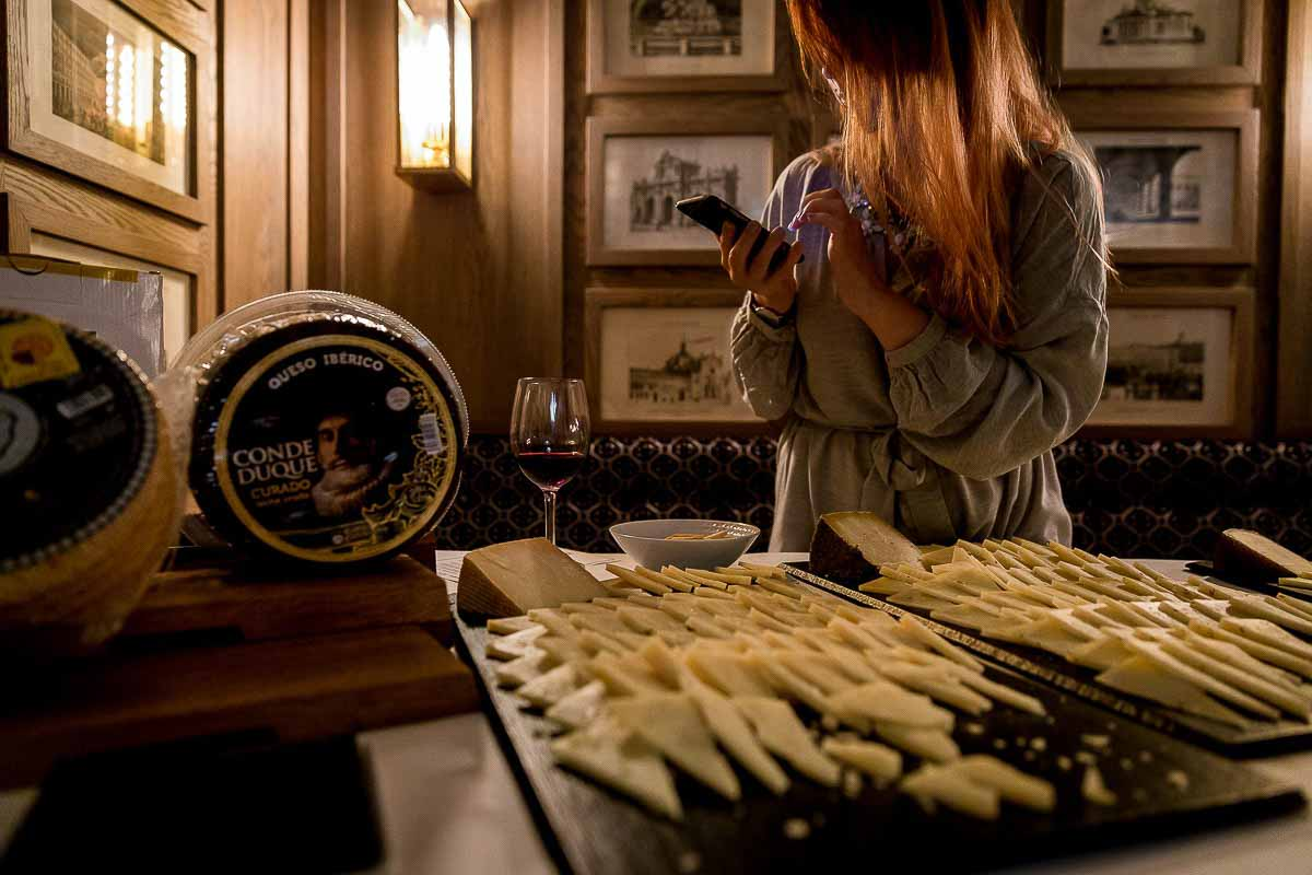 A girl taking a photo of a cheese selection during an event for Hispania Brussels
