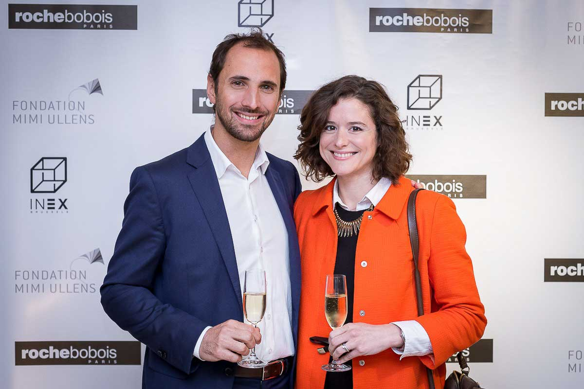A couple smiles in front of a banner during an event for Roche Bobois Brussels