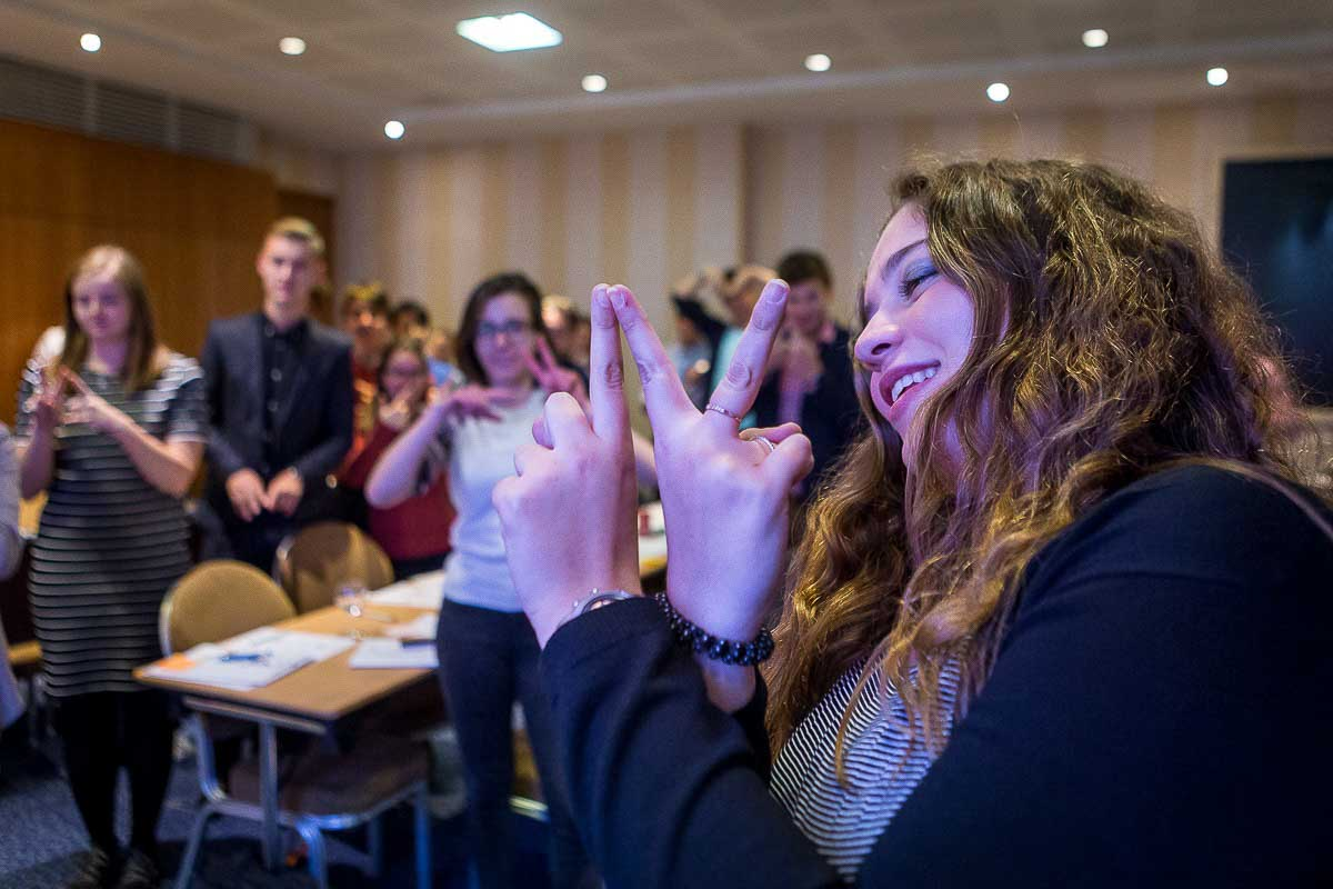 A girl making a sign with her hands during a workshop for Leaders for a Day in Brussels