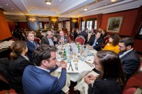 A group of people sitting on a table during a lunch event featuring Roberto Viola in Brussels