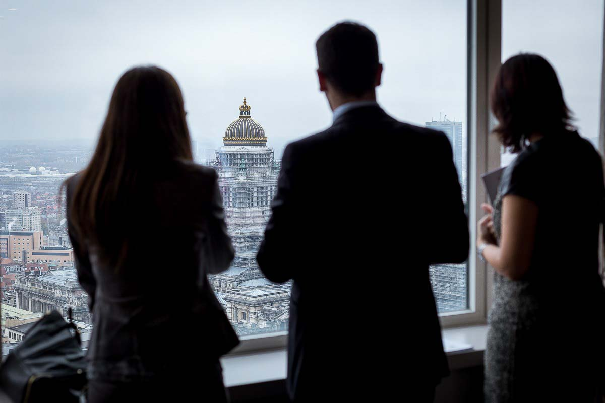 A group of people become silhouettes while they look out from The Hotel window in Brussels