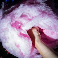 Close up flash street photograph of a big cotton candy from low perspective being held by a hand