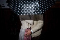 Close up flash street photograph of a couple having an intimate moment under a polka dot umbrella