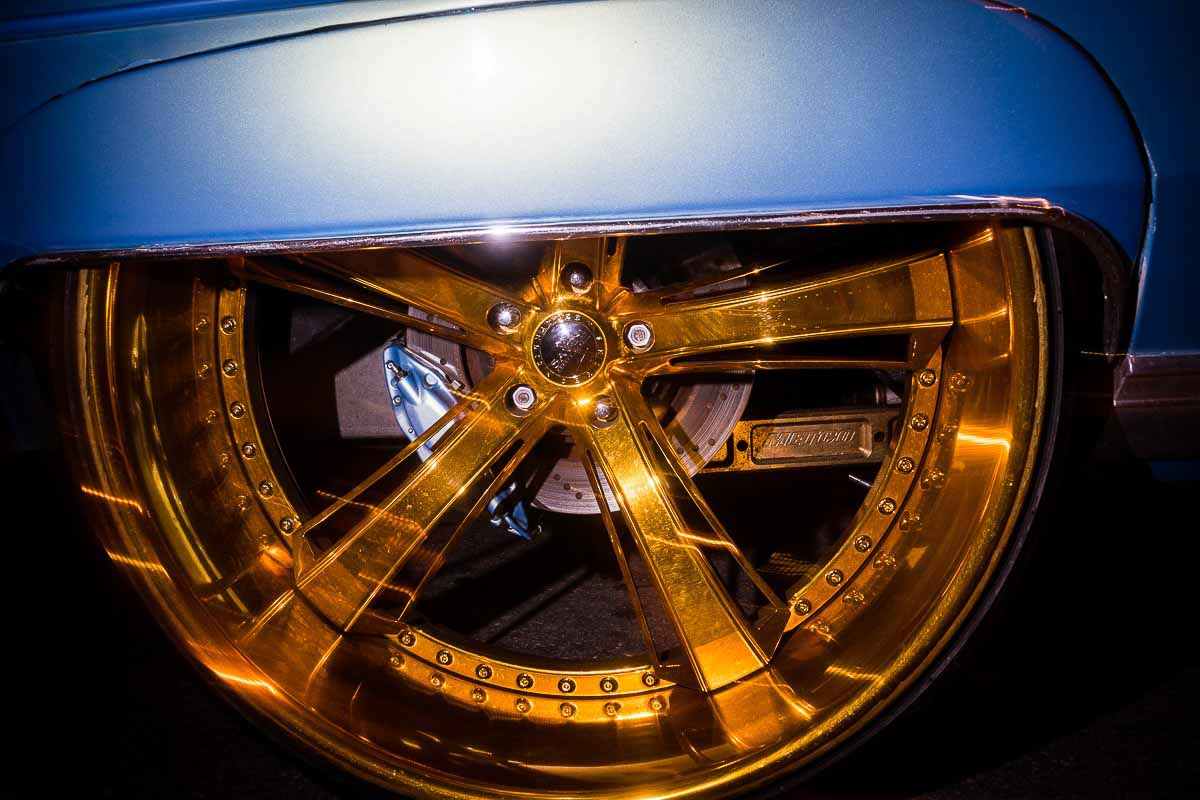 Close up flash street photograph of a gold ring of a blue car's wheel while moving in Miami
