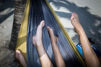 Close up flash street photograph of two people's legs on a hammock in the beach in Miami