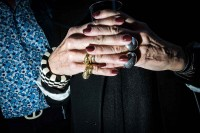 Close up flash street photograph of an elder woman's hands interlaced with each other