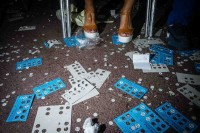 Close up flash street photograph of a woman's feet standing in front of many Bingo cartons