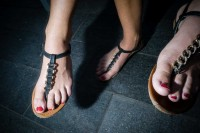 Close up flash street photograph of three feet wearing sandals in Budapest