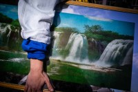 Close up flash street photograph of a someone's arm carrying a painting of a waterfall