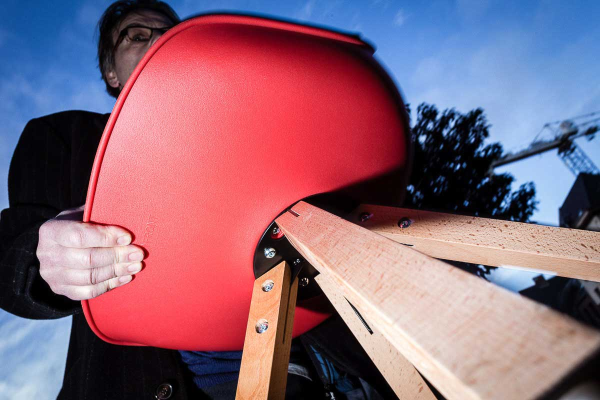 Close up flash street photograph of a man carrying a red chair seen from low perspective towards up