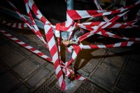 Close up flash street photograph of a scaffolding holding red and white tape