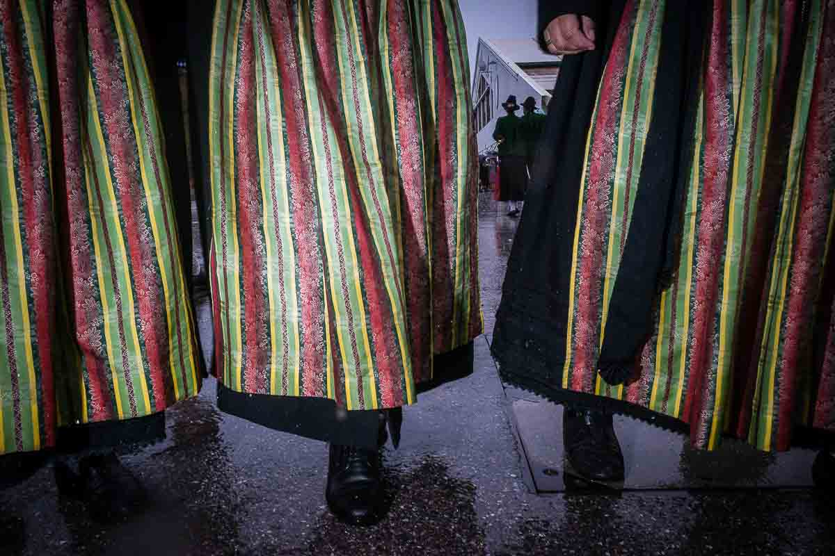 Close up flash street photograph of 3 women walking wearing traditional Bavarian dresses