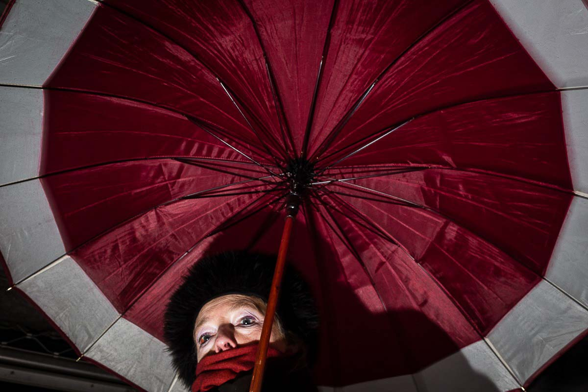 Close up flash street photograph of a woman under an umbrella taken from below