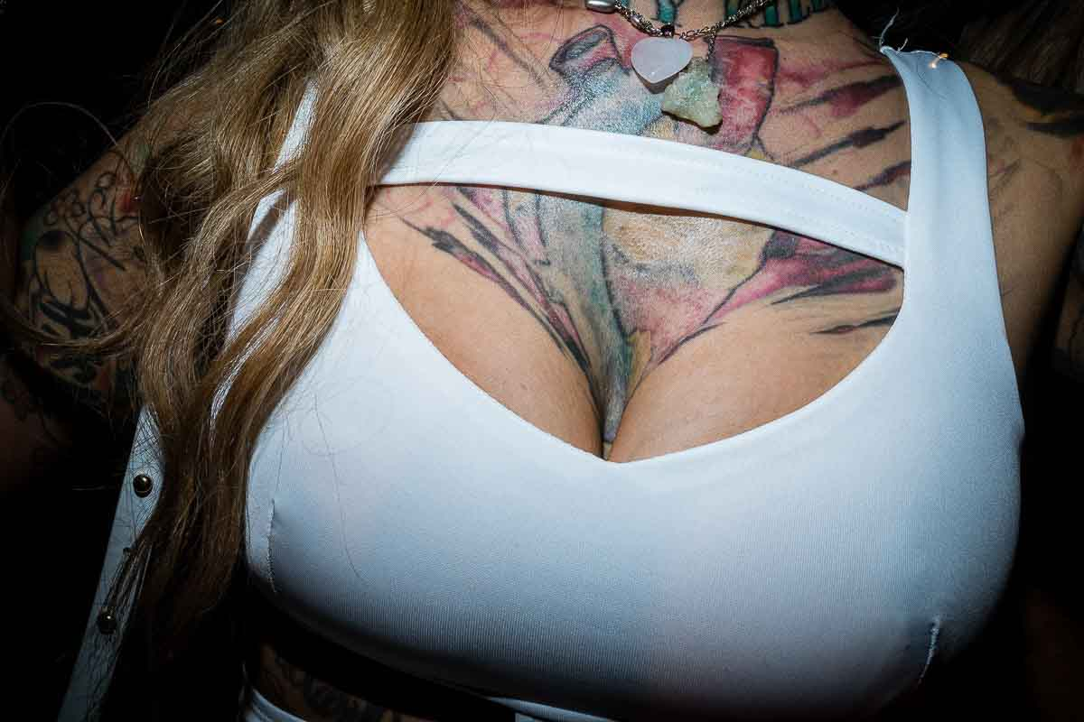 Close up flash street photograph of a woman's chest which has a big tattoo in Miami