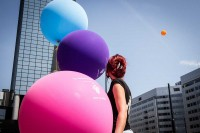 A woman next to three big balloons while she looks up the sky where a fourth balloon can be seen