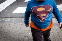 Closeup of a chubby's child torso wearing a blue t-shirt with the emblem of Superman in Brussels