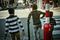 Three boys wearing black and white horizontal stripes shirts waiting in a street light to cross