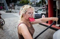 A woman holding a red card with her teeth while she pumps her car with gasoline in Brussels