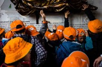 A group of children wearing orange caps and hats raising their hands to touch a famous statue