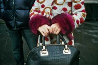 Closeup of the hands of a woman wearing a fancy coat with violet spots and fur carrying a black bag