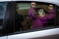 Street Photograph of a girl apparently trying to get off a car by the window