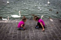 A couple of girls laying on their knees facing each other in mirror positions in front of a lake