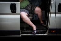 Street scene of a man's legs seen inside a van truck that has its door open in Brussels