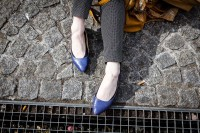 Street scene of a woman's very pale feet wearing blue sandals and dark gray pants in Paris