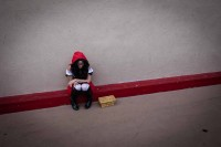 A street performer dressed as red riding hood while sitting in a corner all alone in Los Angeles