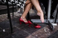 A street scene of a woman's legs wearing red shoes while she's sitting down in Brussels