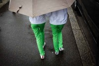 A couple of girls dressed with green pants and white sweatshirts covered by a large umbrella