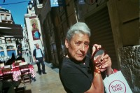 An elder woman holding a hand mirror while nipping her eyebrows with an eyebrow nipper