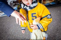 Close up flash street photograph of a child wearing a yellow jacket holding a teddy duck