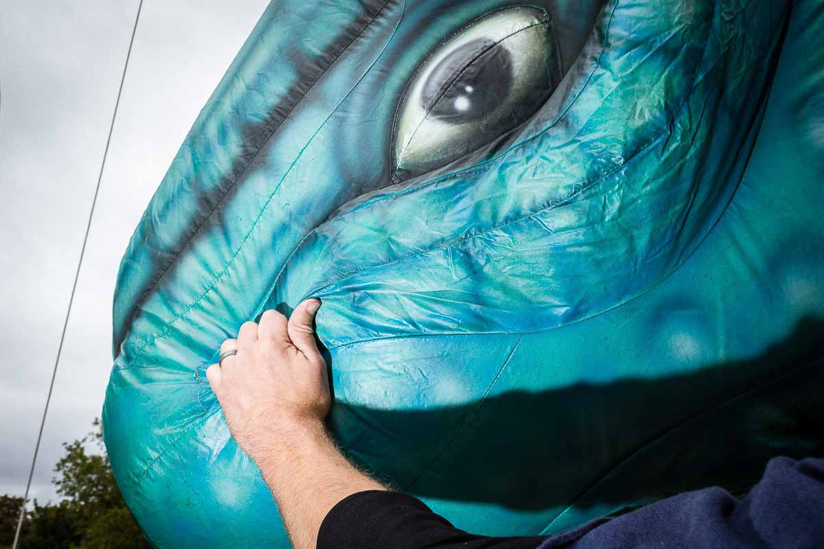 Close up flash street photograph of a hand grabbing an inflatable upside down green dinosaur head