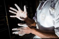 Close up flash street photograph of black man with his hands covered in white flour in Brussels