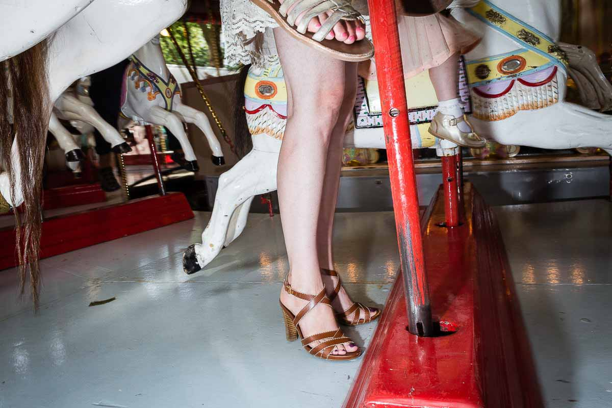 Close up flash street photograph of woman's legs next to a carousel horse