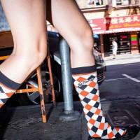 Close up flash street photograph of a pair of legs wearing high colored socks walking
