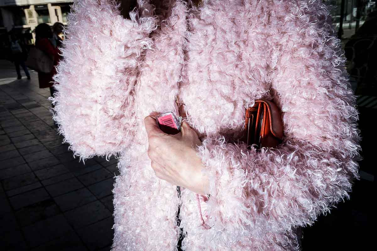 Close up flash street photograph of the torso of a woman wearing a pink fluffy coat