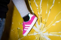 Close up flash street photograph of a child's foot wearing a pink shoe against a yellow wall