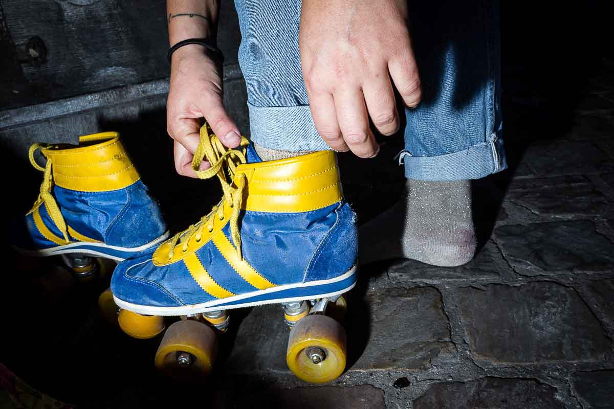 Close up flash street photograph of person fixing their blue and yellow roller skates