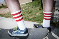 A foot of a man over a skateboard wearing white socks with 3 red horizontal stripes
