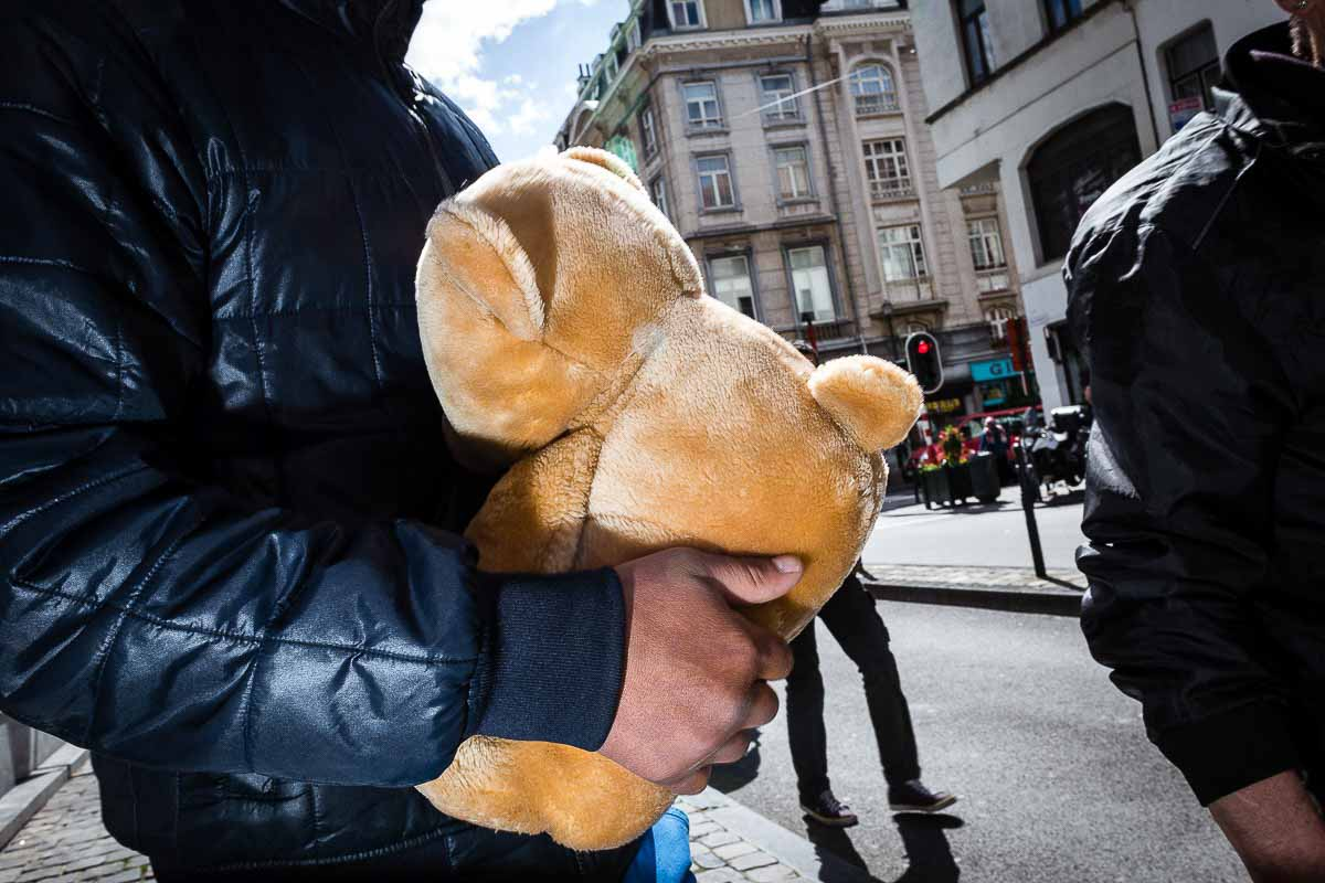 Close up flash street photograph of man carrying a teddy bear in Brussels
