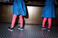 Close up flash street photograph of two girls seen from behind wearing blue dresses and pink socks