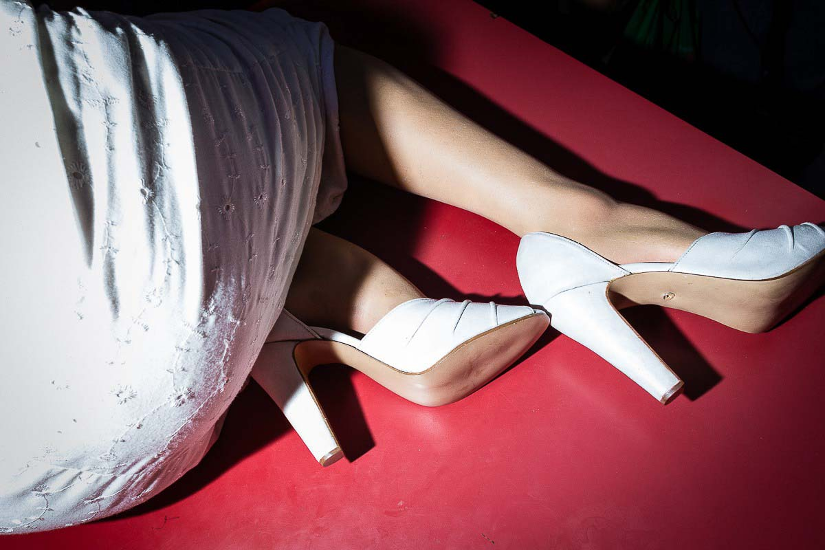 Close up flash street photograph of a woman wearing a white dress and shoes laying on a red floor
