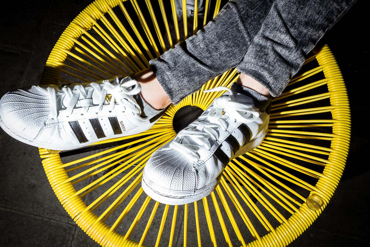 Close up flash street photograph of a pair of feet wearing Adidas shoes on top of a yellow chair