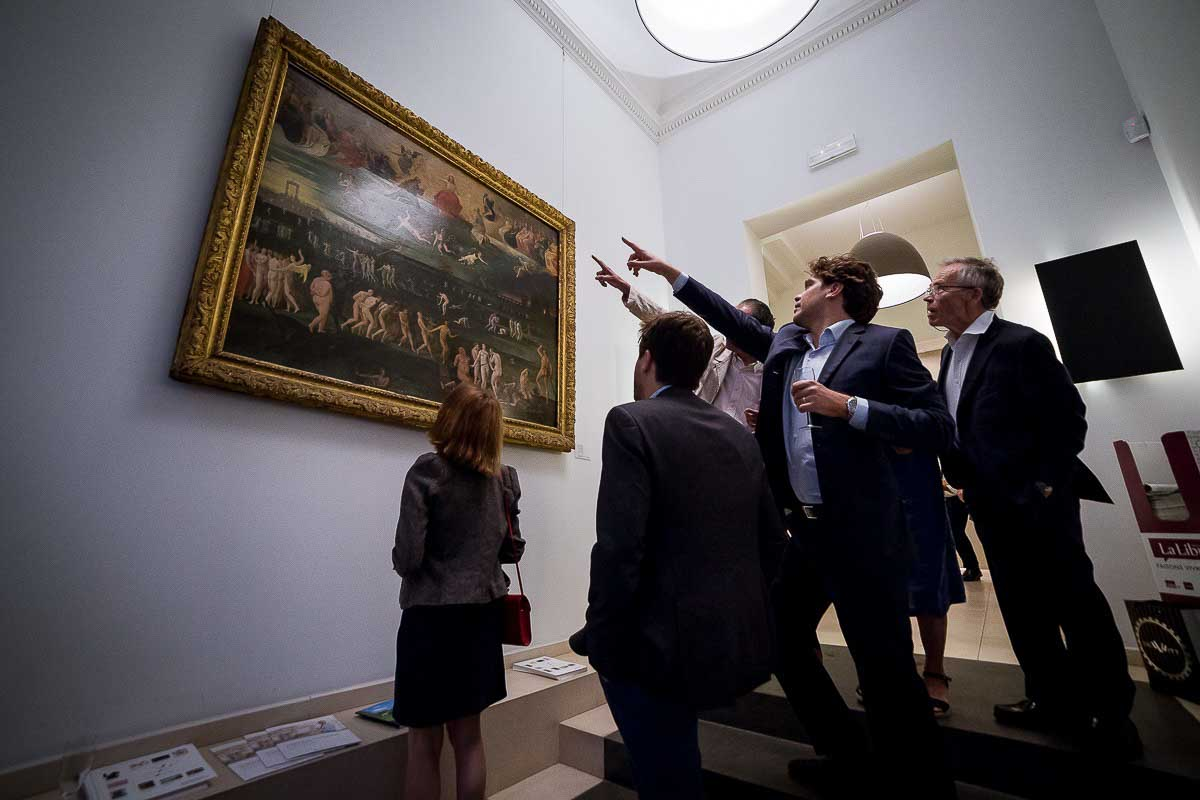 Visitors admiring a painting during an art exhibition event by Sotheby's in Brussels