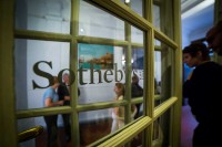 Visitors seen through a window during an art exhibition event by Sotheby's in Brussels