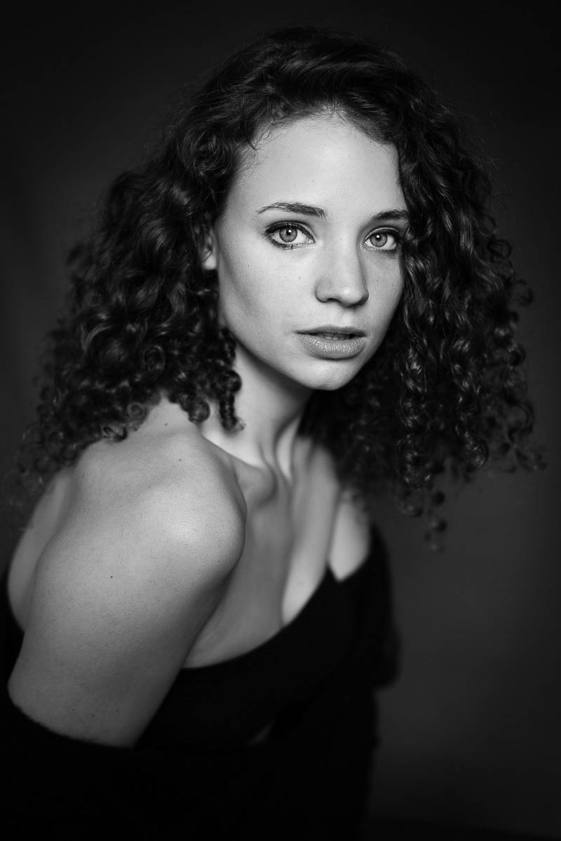 Black and white headshot portrait of young woman with curly hair
